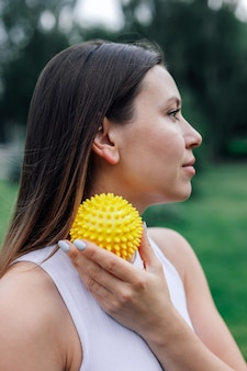 Close  up portrait in profile of young woman face blured with spiky massage ball for myofascial rele...