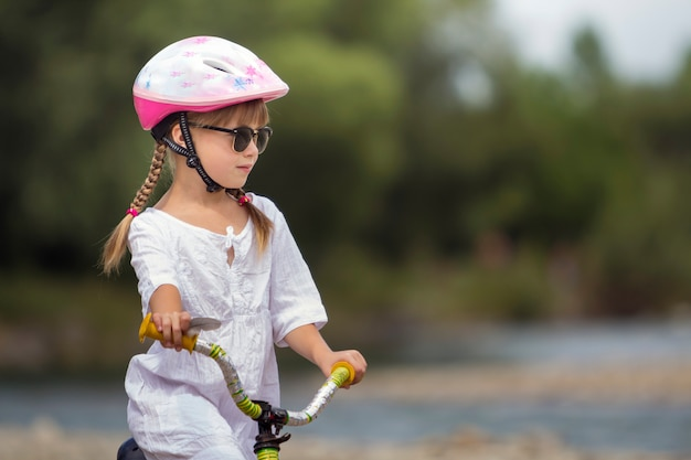 Close-up portrait of proud pretty young girl in white clothing, sunglasses with long blond braids wearing pink safety helmet riding child bicycle on blurred green trees summer