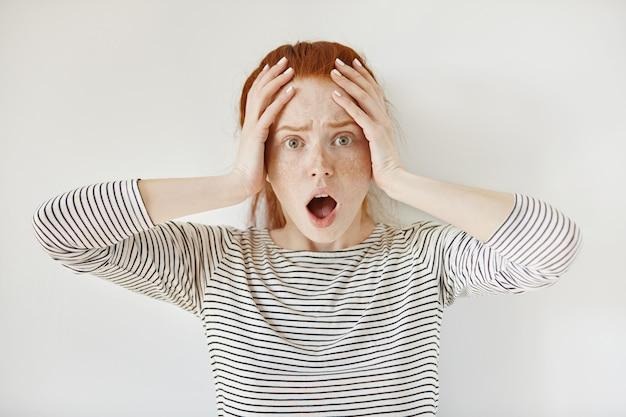 Close up ritratto di ragazza studentessa caucasica rossa perplessa e spaventata che indossa top a strisce, mantenendo la bocca aperta e le mani sulla sua testa, guardando con paura, scioccata dai brutti voti agli esami