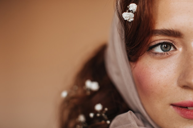 Close-up portrait of red-haired woman in scarf. lady with blush on cheeks and freckles posing on isolated background.