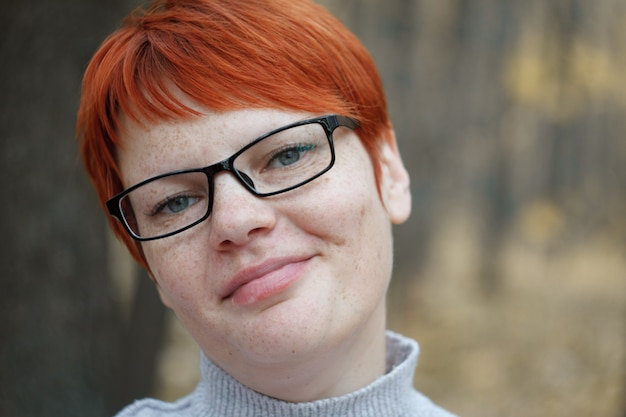 Close-up portrait of a red-haired woman with glasses