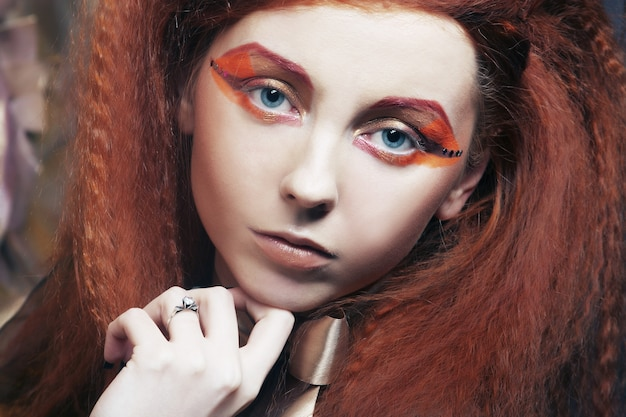 明るい創造的なメイクアップで肖像画のredhair女性をクローズアップ