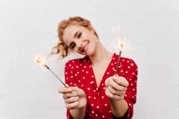 Il ritratto del primo piano del modello femminile caucasico raffinato indossa il pigiama rosso nella mattina del nuovo anno. foto dell'interno della ragazza allegra con luci del bengala in piedi vicino al muro bianco.