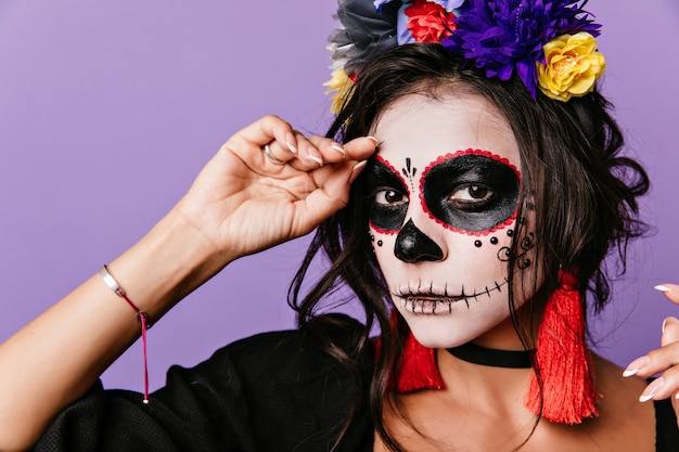 Close-up portrait of refined woman with dark eyes posing in masquerade costume. cute latin lady in flower wreath preparing for halloween.