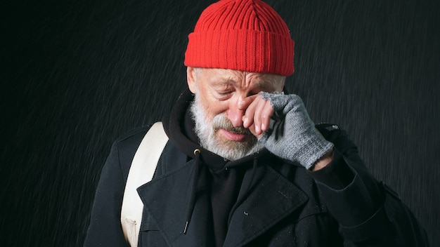 Close-up portrait of a retired 70-year-old man with a wrinkled face, dressed in a coat and red hat, wipes tears from his eyes on an isolated black background