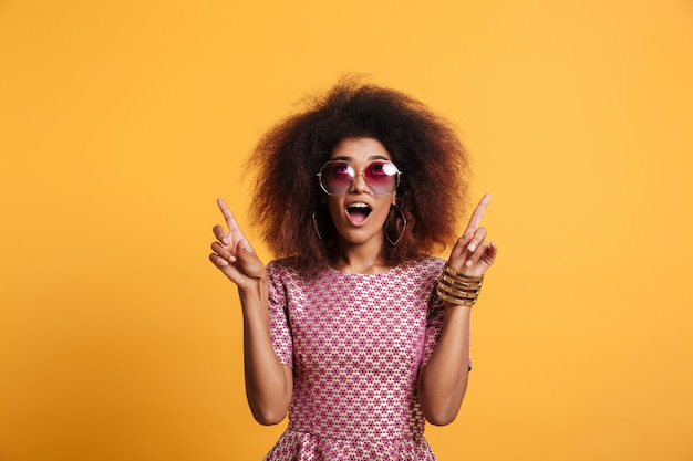 Close-up portrait of retro stylish amazed african wooman in sunglasses pointing with two fingers up, looking upward