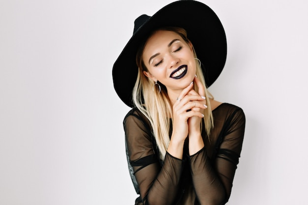 Close up portrait of romantic beautiful woman with dark lips posing over isolated wall with happy smile and closed eyes wearing black hat
