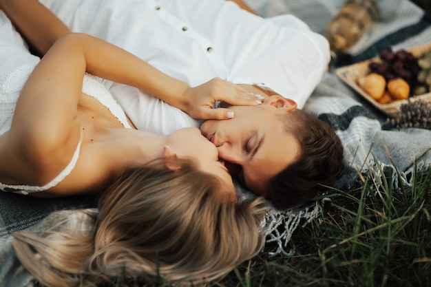 Close up portrait of romantic couple lying on a picnic blanket, hugging and kissing at picnic in the park.