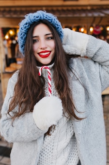 Ritratto del primo piano della ragazza europea romantica con capelli scuri che posano con il lecca-lecca di natale dolce. foto del modello femminile abbastanza caucasico in guanti bianchi e cappello blu divertendosi