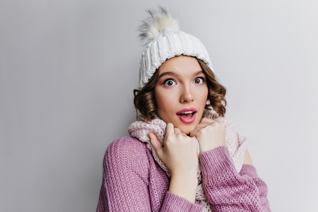 Close-up portrait of romantic pale woman in cute knitted hat isolated on purple wall. pretty brown-eyed girl in white scarf posing