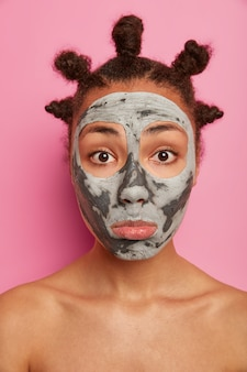 Close up portrait of sad mixed race young woman looks at herself in mirror, applies clay mask on face, stands with bare shoulders, cares about body and complexion, isolated over pink wall.