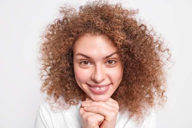 Close up portrait of satisfied young european girl with brown curly hair keeps hands under chin smiles gently hears something pleasant looks directly  isolated over white wall