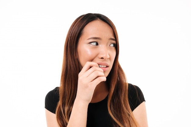 Close-up portrait of scared young asian woman standing with finger in her mouth, lookin aside
