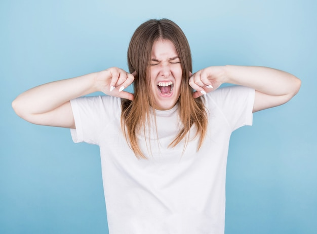 Close-up portrait of screaming young woman covering closed ears and eyes, furious with loud noise