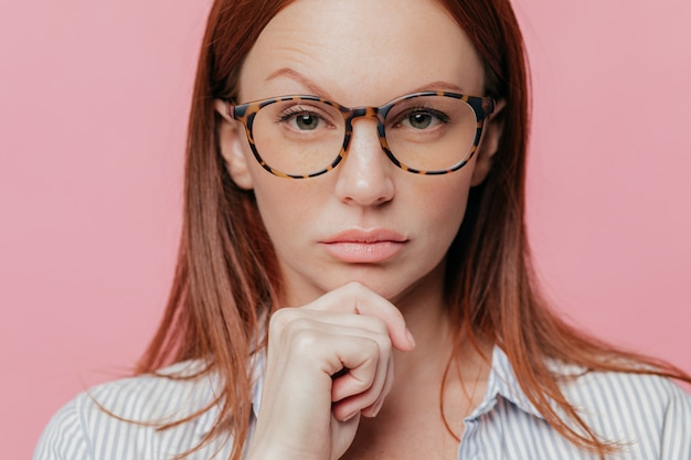 Close up portrait of self confident female business owner holds chin, raises eyebrow, wears optical glasses