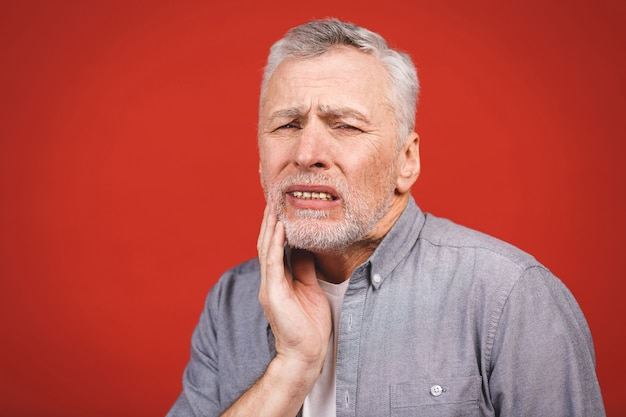 Close-up portrait of senior aged man suffering from toothache o