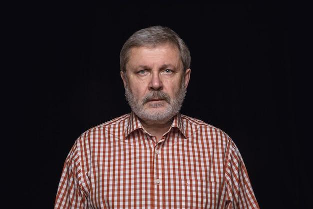 Close up ritratto di uomo anziano isolato su nero di sfondo per studio