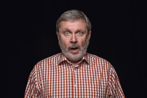 Close up portrait of senior man isolated on black studio wall