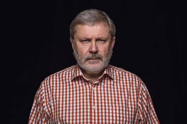 Close up portrait of senior man isolated on black studio