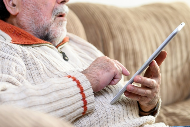 Close up portrait of senior man sitting on sofa and using digital tablet in living room.
