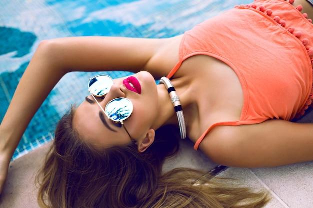 Chiuda sul ritratto della modella sensuale glamour che prende il sole vicino alla piscina privata