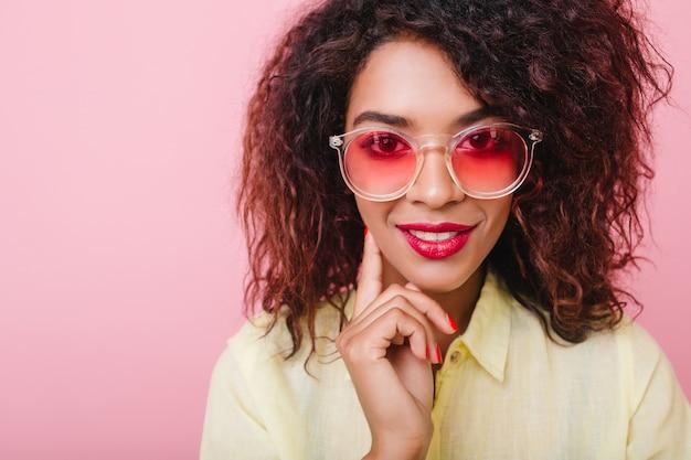 Ritratto del primo piano della ragazza interessata sensuale in occhiali rosa che tocca la guancia con la mano. adorabile signora con pelle marrone e trucco luminoso sorridente.
