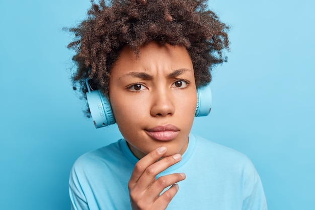 Close up portrait of serious afro american girl keeps hand on chin looks displeased  dressed casually listens music via headphones or learns new foreign words isolated over blue wall
