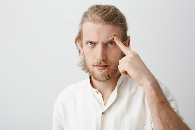 Close-up portrait of serious attractive bearded man with fair hair, lifting eyebrow with index finger as if trying to threaten or scare someone
