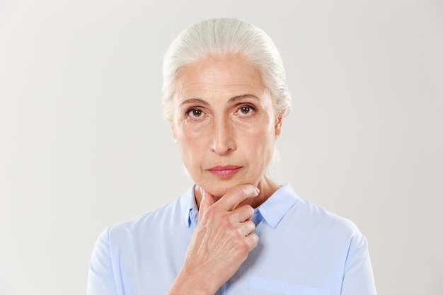 Close-up portrait of serious beautiful old woman, touching her chin