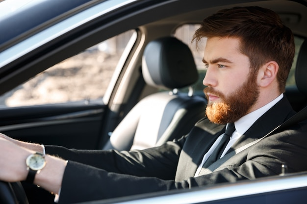 Close up portrait of serious business man driving car