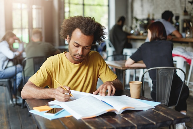 Close-up portrait of serious dark-skinned male student wearing yellow t-shirt sitting at cafe during break drinking coffee and preparing for lessons writing in copybook from book with pencil