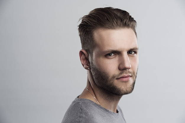Close up portrait of serious gloomy bearded man with stylish hairstyle posing against white background.