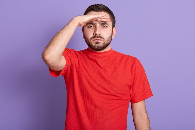 Close up portrait of serious handsome bearded man looking into distance, holding hand at forehead, posing isolated against purple wall
