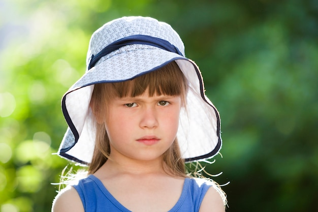 Close-up portrait of serious little girl in a big hat.