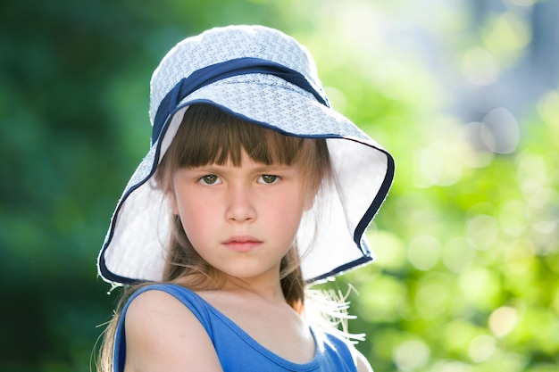 Close up portrait of serious little girl in a big hat