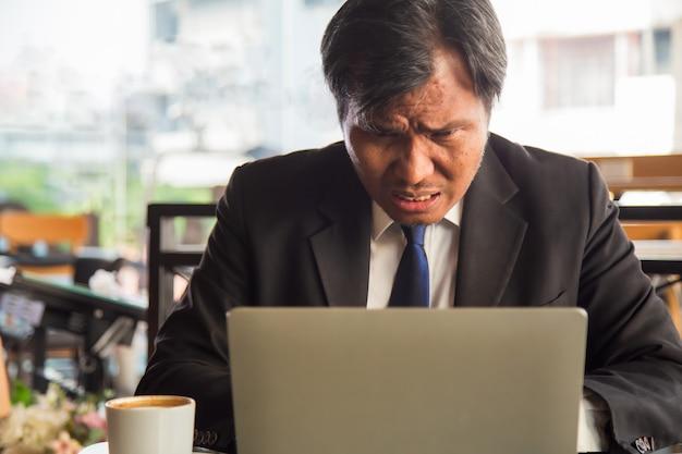 Закройте вверх по портрету серьезного бизнесмена среднего возраста азиатского используя компьтер-книжку с кофейной чашкой на стороне на современном офисе.