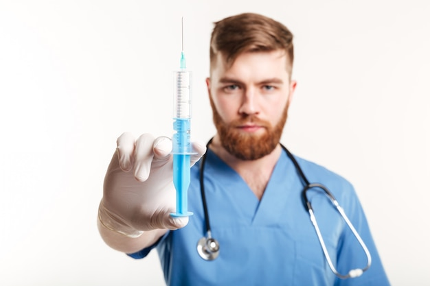 Close up portrait of a serious surgeon holding a syringe