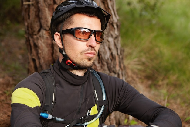 Close up portrait of serious and thoughtful rider with stubble wearing cycling clothing, protective helmet and glasses sitting outdoors at tree and looking ahead of him, thinking about his life