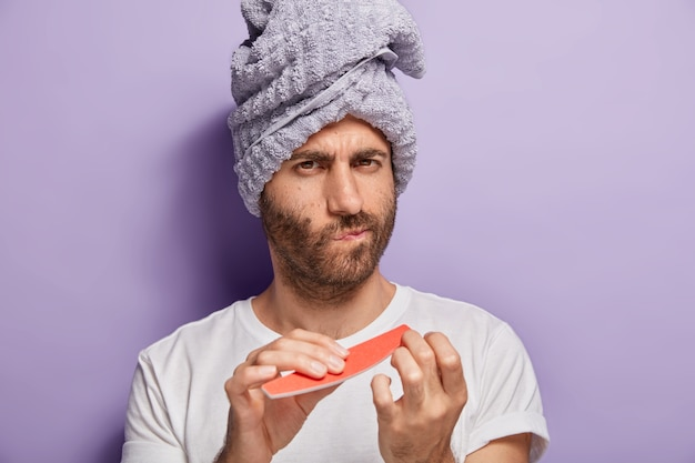 Close up portrait of serious unshaven man with soft towel on head, does manicure after taking shower, uses nail file, cares about his beauty, wears white t shirt, isolated on purple wall