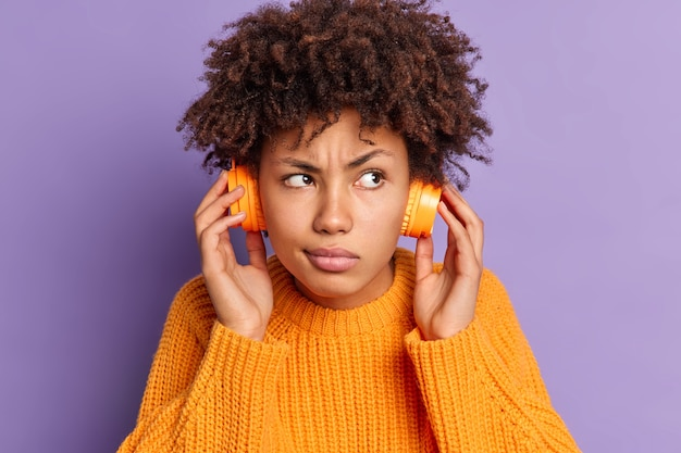 Close up portrait of serious young african american woman listens audio track concentrated somewhere wears wireless headphones poses