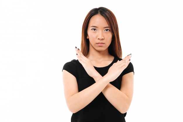 Close-up portrait of serious young asian lady showing stop gesture with crossed hands, looking at camera