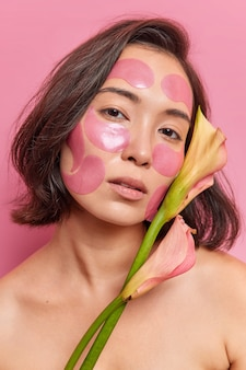 Close up portrait of serious young asian woman with short dark hair applies hydrogel patches on face to refresh skin holds flower stands naked against pink wall undergoes beauty procedures.