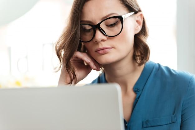 Chiuda sul ritratto di una giovane donna seria in occhiali