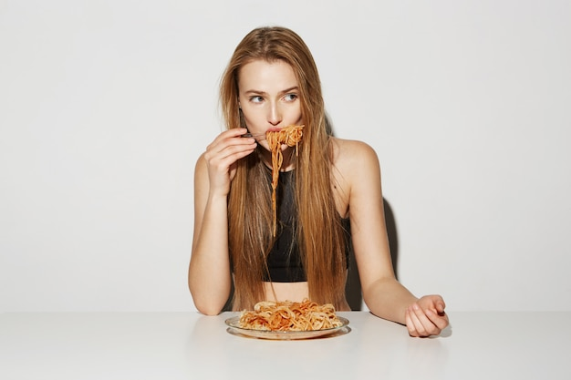 Close up portrait of sexy blonde girl with long hair sitting at table, eating spaghetti, looking aside with relaxed and flirty expression.