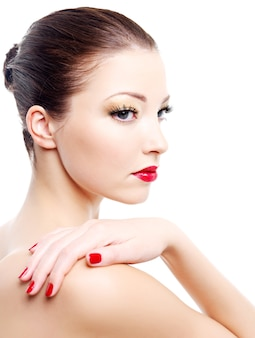 Close-up portrait of sexy caucasian young woman with golden glamour make-up and red bright manicure