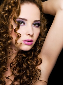 Close-up portrait of a sexy young beautiful  woman with beauty hairs.  isolated on a black