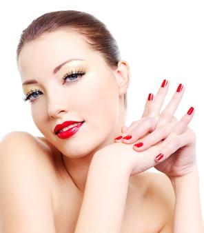 Ritratto del primo piano di giovane donna sexy con trucco glamour dorato e manicure lucida rossa