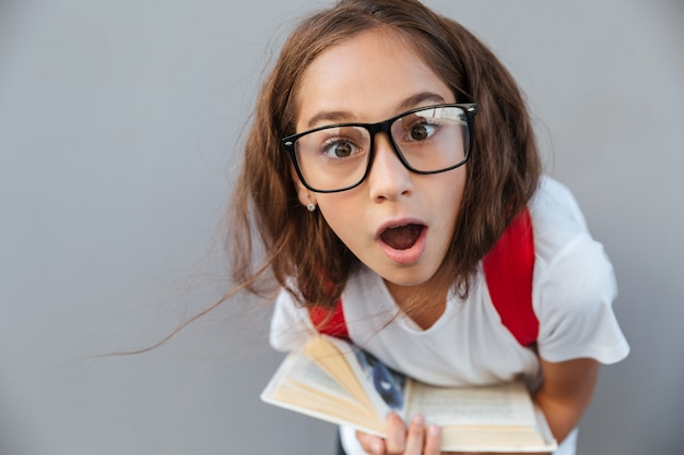 Close up portrait of shocked brunette schoolgirl in eyeglasses