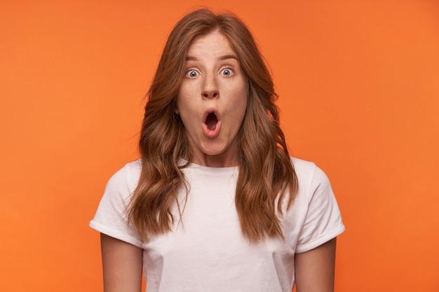 Ritratto del primo piano della donna riccia scioccata in maglietta bianca in posa con la faccia con gli occhi aperti, alzando le sopracciglia e aprendo ampiamente la bocca