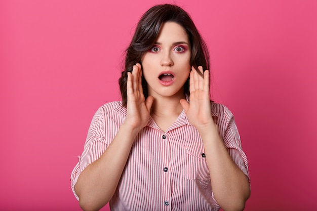 Close up portrait of shocked girl with her mouth opened, keeps near face, modelposing isolated over pink studio background, wearing blouse, having dark hair, looks scared. people emotions concept.